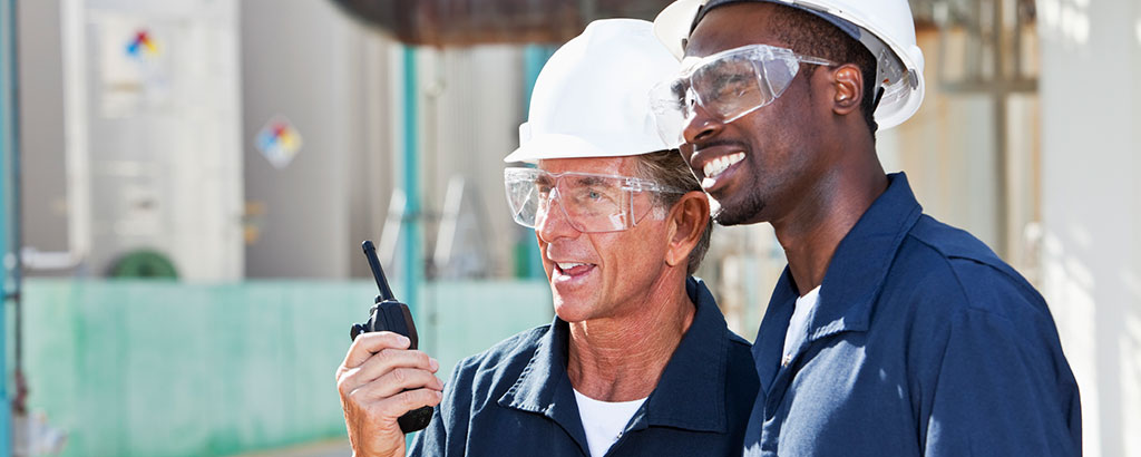 two workers with hard-hats communicating with a hand-held two-way radio